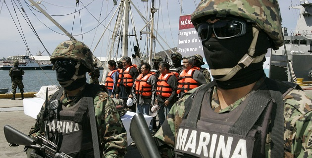 Mexican marines stand guard next to five arrested crew members at a naval base in Salina Cruz in Mexico's state of Oaxaca May 3, 2010. Mexico intercepted a ship in international waters in the Pacific Ocean carrying 2,400 kg of cocaine. REUTERS/Jorge Luis Plata (MEXICO - Tags: POLITICS CRIME LAW)