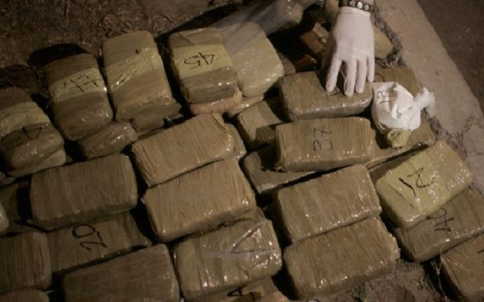 A federal police officer arranges packages of marijuana and a bag of cocaine seized in a house allegedly occupied by drug dealers during an operation in Ciudad Juarez, Mexico,  Monday, March 9, 2009. Mexico's cartels are losing their grip on the prized U.S. drug market, largely because of a cross-border crackdown and a regional shift in worldwide cocaine consumption.(AP Photo/Miguel Tovar)