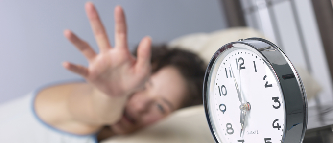 Woman in bed reaching for alarm clock