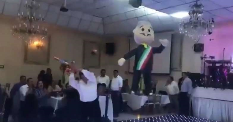 Perredistas rompen piñata de AMLO en su posada