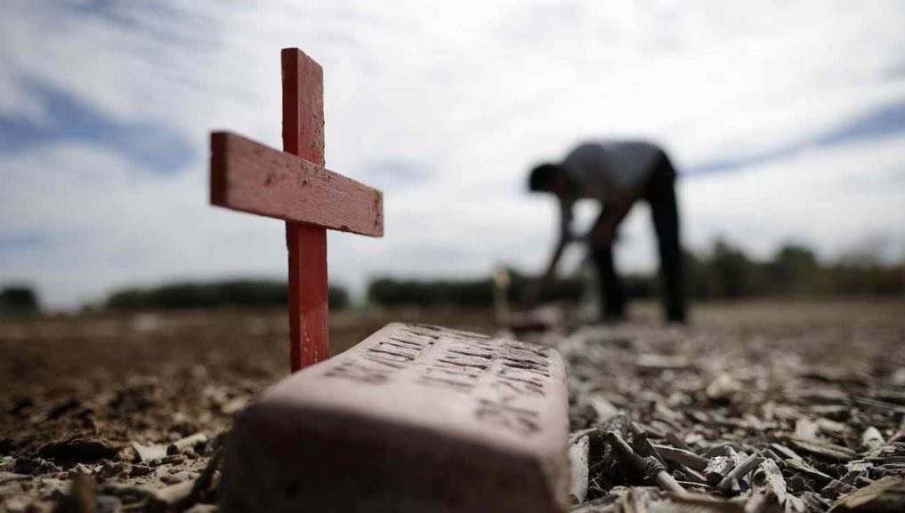 Jesus Salvador places crosses in a pauper's cemetery where hundreds of unidentified migrants are buried Tuesday, Feb. 14, 2017, in Holtville, Calif. As part of a Valentine's Day celebration, a group from San Diego and the Imperial Valley replaced wooden crosses on the graves in this dirt field Tuesday, the final resting place for hundreds of migrants killed while attempting to illegally cross the U.S. - Mexico border through the nearby mountains and desert. (AP Photo/Gregory Bull)