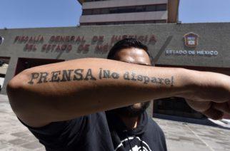 """TOLUCA, ESTADO DE MÉXICO, 29AGOSTO2019.-  Periodistas del Estado se Mexico se manifestaron en la Fiscalía General de Justicia estatal (FGJEM) exigiendo se aclare el asesinato de Nevith Condés Jaramillo en el municipio de Tejupilco. con un performance atándose con cadenas y pintada de rojo simulando sangre y una manta que dice """"Informar no es un crimen No se mata la verdad matando periodistas"""". FOTO: CRISANTA ESPINOSA AGUILAR /CUARTOSCURO.COM"""