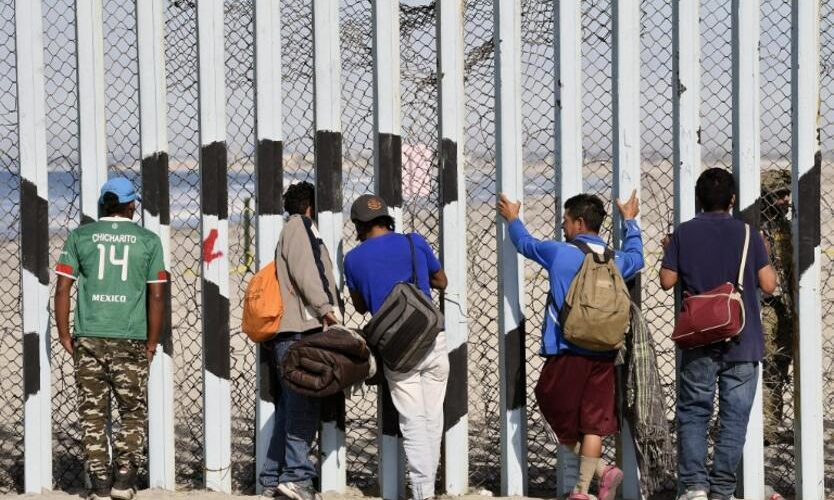 """Central American migrants -mostly Hondurans- moving towards the United States in hopes of a better life, remain by the U.S.-Mexico border fence in Playas de Tijuana, Mexico, on November 15, 2018. - US Defence Secretary Jim Mattis said Tuesday he will visit the US-Mexico border, where thousands of active-duty soldiers have been deployed to help border police prepare for the arrival of a """"caravan"""" of migrants. (Photo by ALFREDO ESTRELLA / AFP)"""